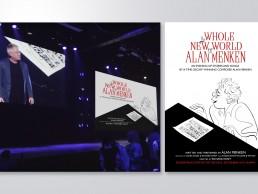 Composer Alan Menken stands on stage next to key art poster