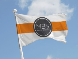 The MBS Media Campus orange, white & gray flag waving in air